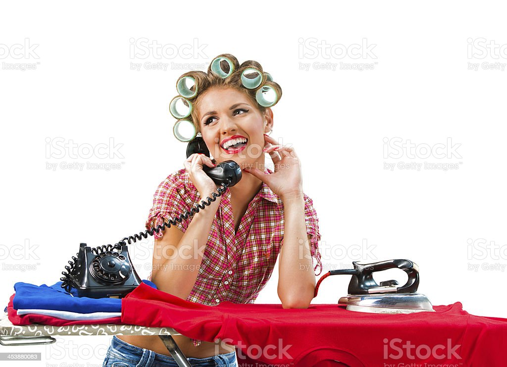Housewife talking on the phone while ironing royalty-free stock photo