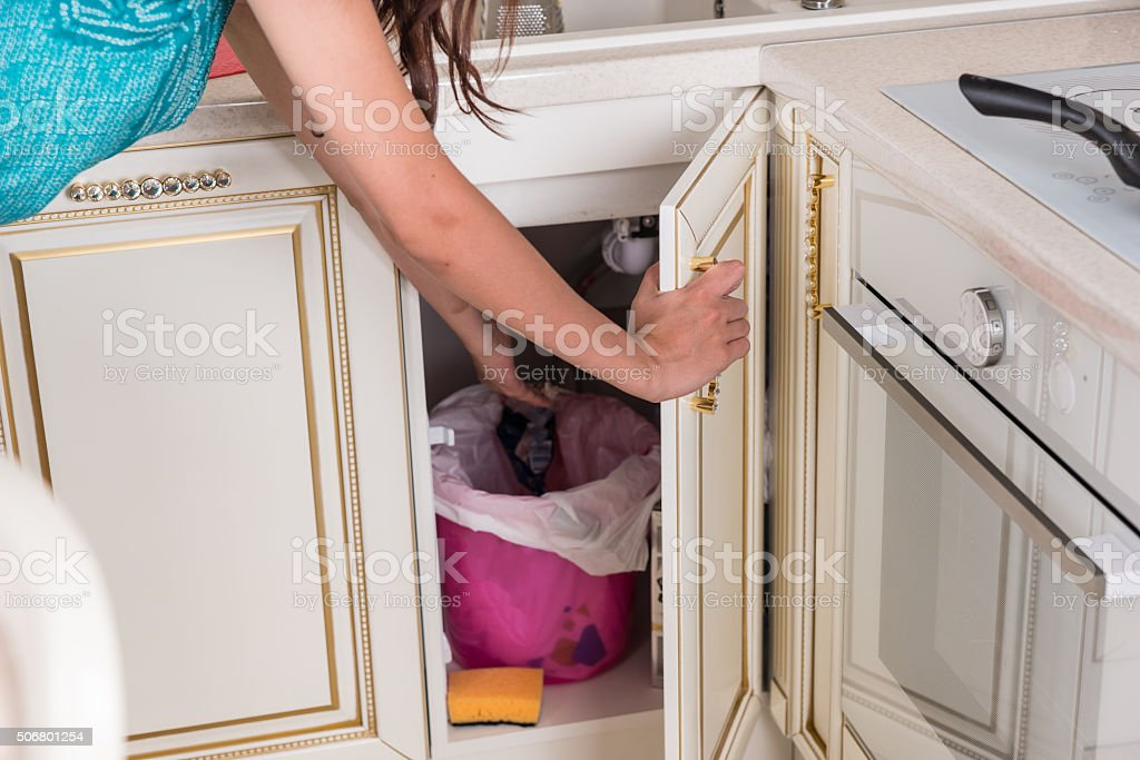 Housewife throwing out garbage in the kitchen stock photo