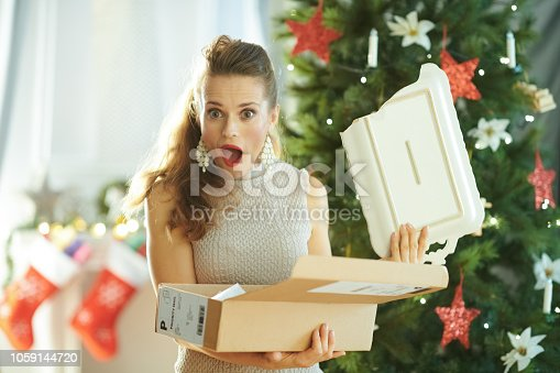 1059144984 istock photo housewife with broken dish from parcel near Christmas tree 1059144720