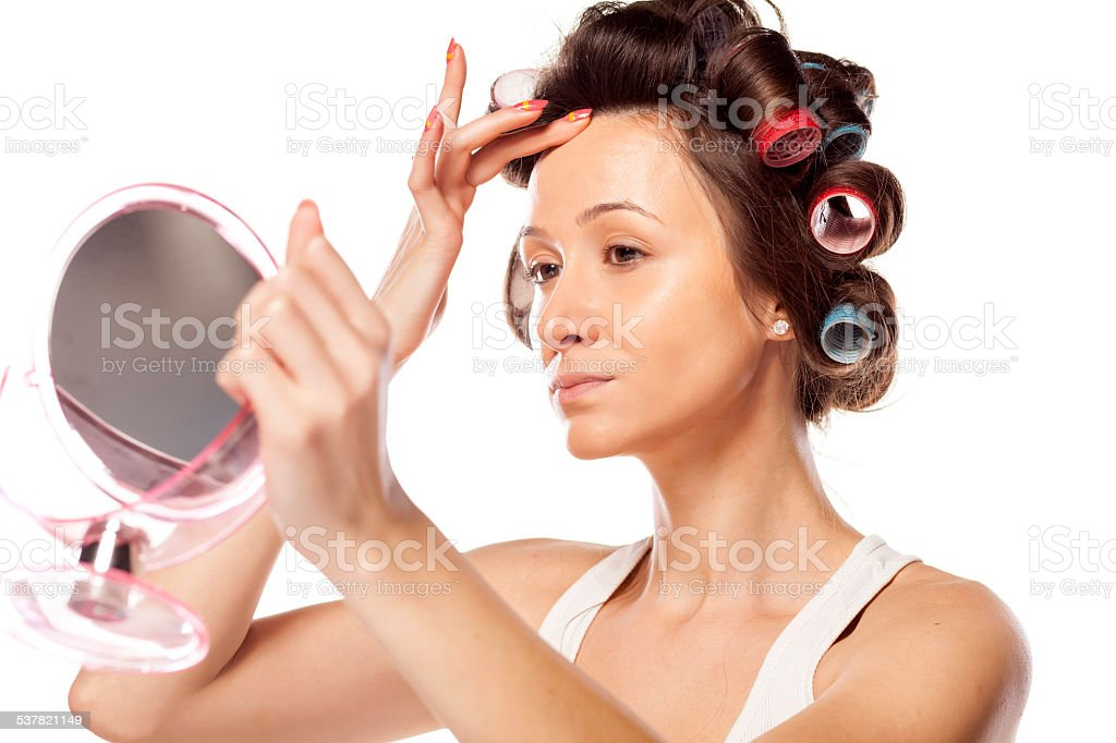 Housewife with curlers applying liquid foundation on her face stock photo