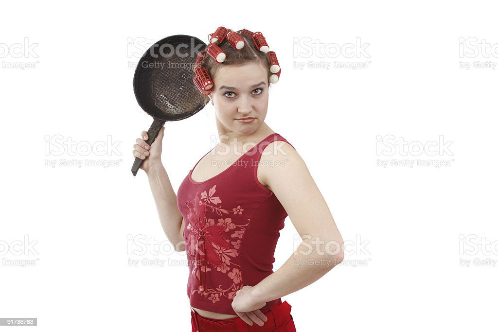 Housewife with curlers in her hair, holding a frying pan. stock photo