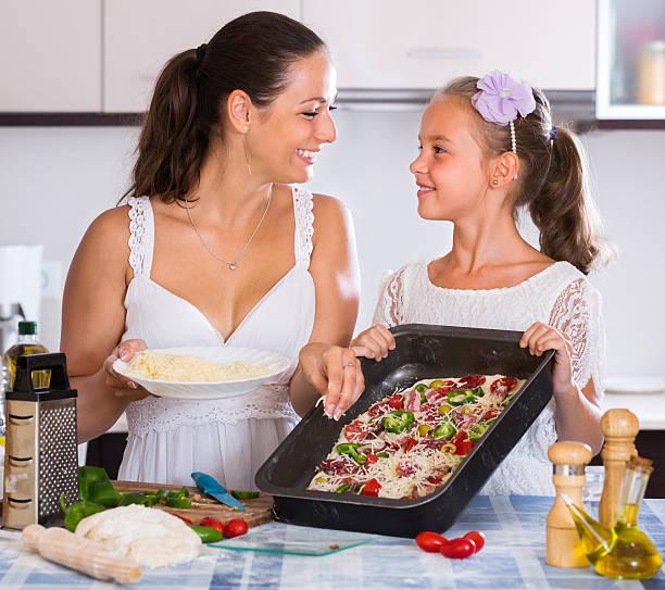 housewife with girl cooking pizza - kabelspek stockfoto's en -beelden