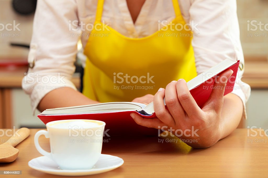 Housewife woman reading cookbook in kitchen. stock photo