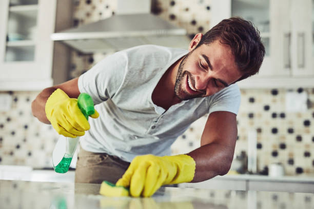 Housework is not just for women Shot of a handsome young man cleaning his home cleaner stock pictures, royalty-free photos & images