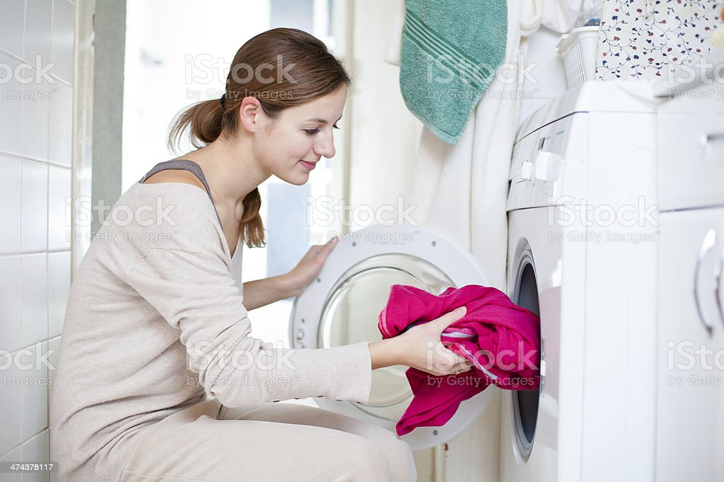 Housework: young woman doing laundry stock photo