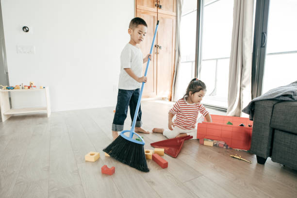 Houseworks for kids A boy is sweeping the floor while his sister is putting thr toys inside the box. kids cleaning up toys stock pictures, royalty-free photos & images