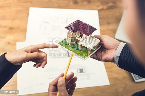 istock A housing developer holding model and explaining concept to client 952643832