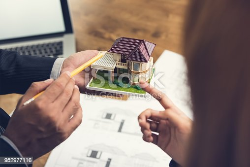 istock A housing developer holding model and explaining concept to client 952977116
