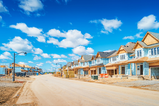 Houses are under construction in a new residential district on a sunny day.