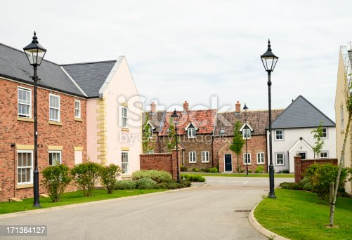Brick houses and traditional landscaping on a quiet street in England in front of a gray sky.  The housing estate has old-fashioned streetlamps.