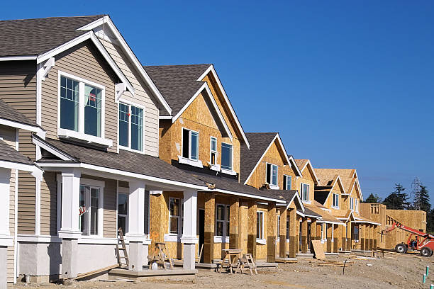 Housing Development Under Construction Perspective photo of a row of similar style houses during various phases of construction. residential district stock pictures, royalty-free photos & images