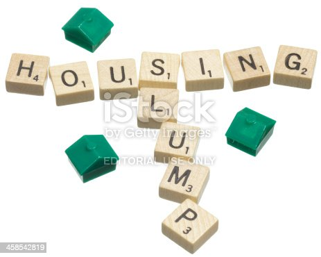 Sacramento, California, USA - February 13, 2012: Scrabble game tiles form the words housing and slump, with an aeriel view of 3 plastic Monopoly houses. Scrabble and Monopoly are registered trademarks of Hasbro, Inc.