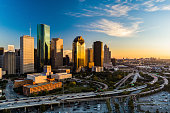 Downtown Houston skyline aerial at sunset with a highway in the foreground, angled view with the Texas Medical Center in the far distance