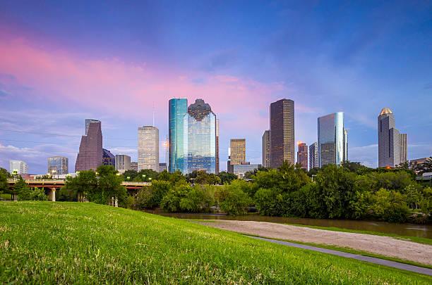 houston, texas-skyline bei sonnenuntergang in der dämmerung vom park lawn - houston texas stock-fotos und bilder