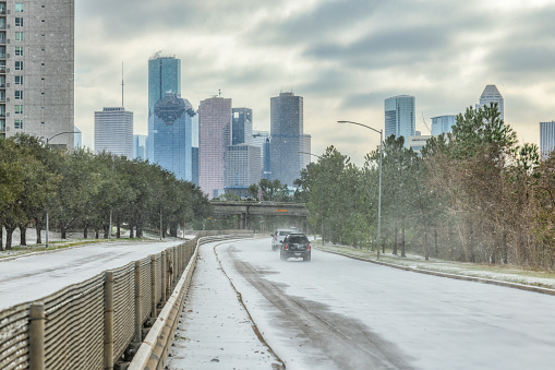Houston, United States - February 15, 2021:  Vehicles navigating the snow and ice on Memorial Drive into downtown Houston as Winter Storm Uri unleashes record cold temperatures in southeast Texas.