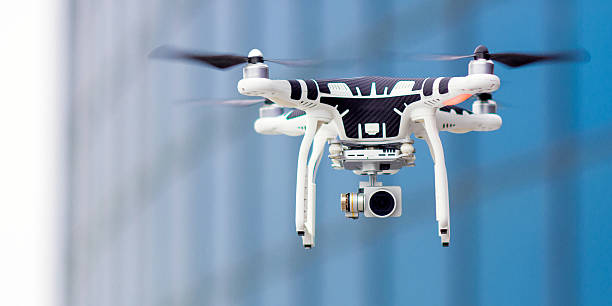 hovering drone that takes pictures - drones stock photos and pictures