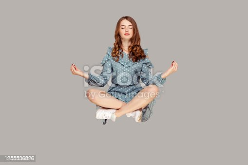 istock Hovering in air. Calm peaceful relaxed girl ruffle dress levitating with mudra gesture hands up, closed eyes, meditating 1255536826