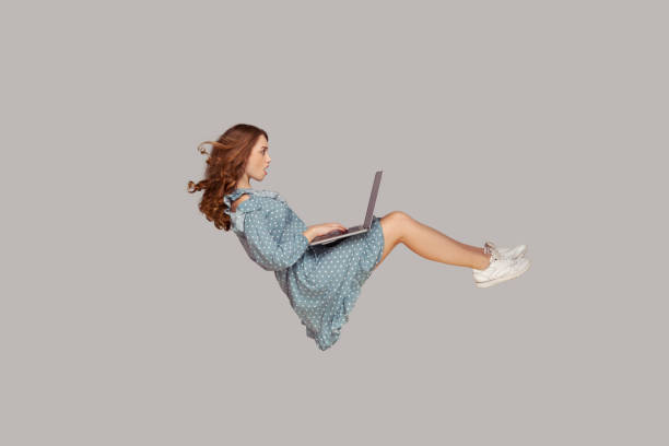 Hovering in air. Surprised girl ruffle dress levitating, looking at laptop screen shocked amazed, surfing web social networks stock photo