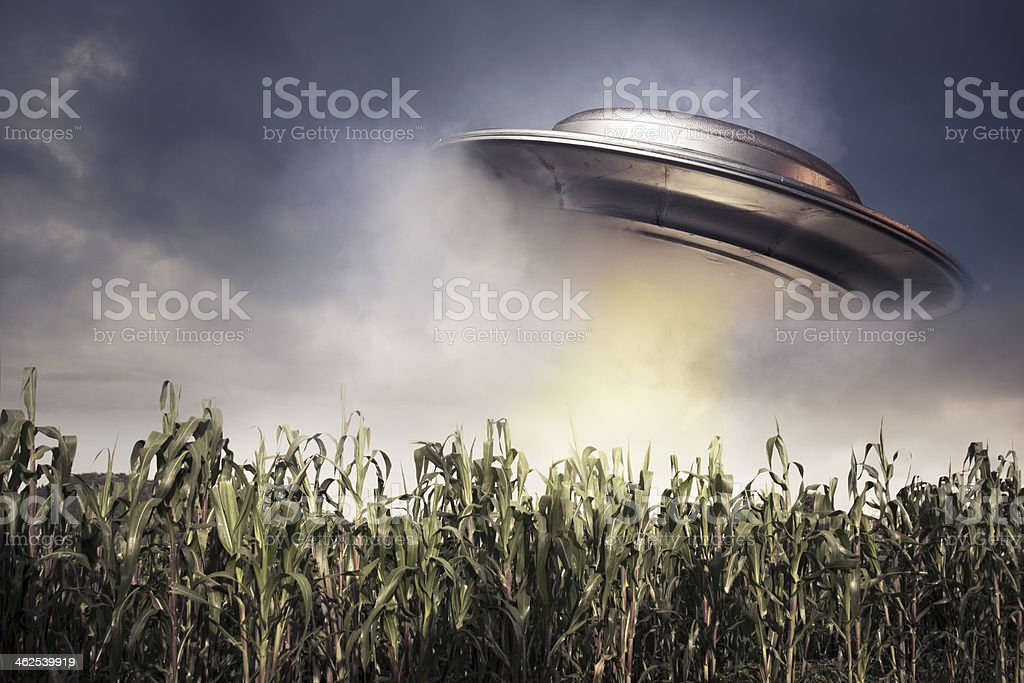 UFO hovering over a crop field stock photo