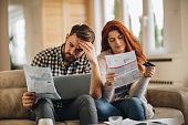 Worried couple feeling frustrated while have to pay their bills over Internet.
