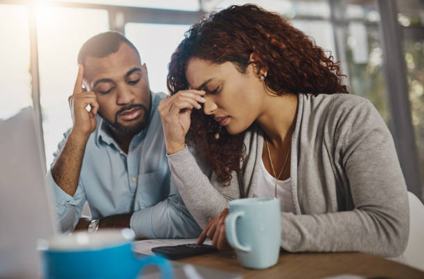 How did we manage to land ourselves in debt? Shot of a young couple looking stressed out while working on their budget at home diad stock pictures, royalty-free photos & images