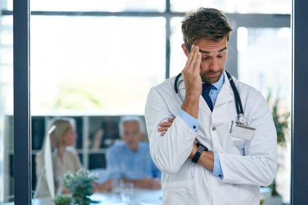 How do I break this terrible news to them? Cropped shot of a doctor looking stressed out with two  patients sitting in the background mental burnout stock pictures, royalty-free photos & images