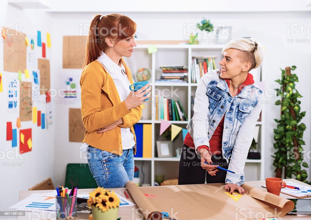 Two young modern businesswomen working in office on creative project...