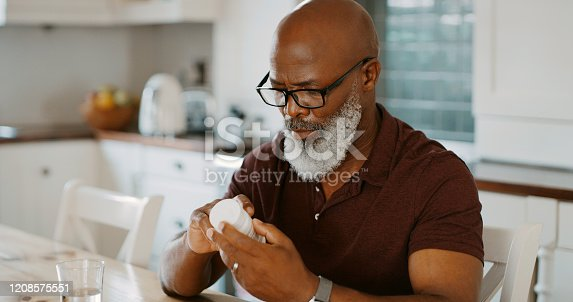 Cropped shot of a senior man sitting alone in his kitchen and taking pills