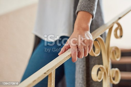 Shot of an unrecognisable woman walking down a flight of stairs