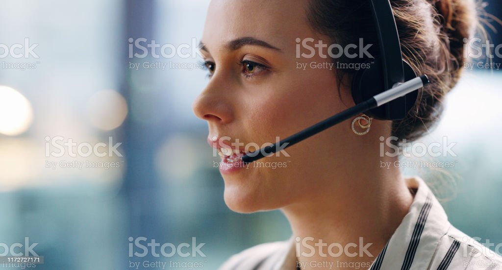 How may I be of service to you? Cropped shot of an attractive young businesswoman wearing a headset and sitting alone in the office during the day 20-29 Years Stock Photo