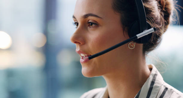 How may I be of service to you? Cropped shot of an attractive young businesswoman wearing a headset and sitting alone in the office during the day call centre photos stock pictures, royalty-free photos & images