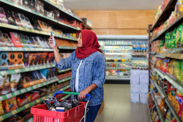 How much sugar in this chocolate bar Photo of a Southeast Asian muslim woman reading food label of a chocolate bar during her weekly grocery shopping snack aisle stock pictures, royalty-free photos & images