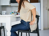 Shot of a young woman adjusting a cushion and chair while working from home