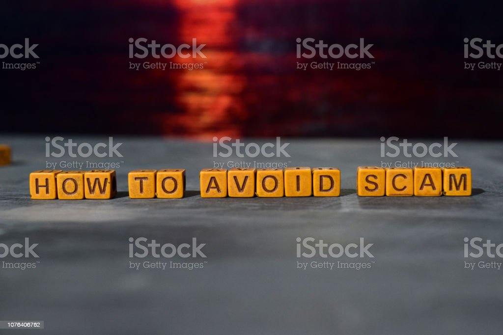 How to avoid scam? on wooden blocks How to avoid scam? on wooden blocks. Cross processed image with bokeh background Alertness Stock Photo