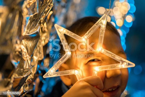 Happy cute boy the elementary age is looking through shining electric star. Studio shooting at holiday Christmas lighting with defocused bokeh light. A shining glittering glowing background