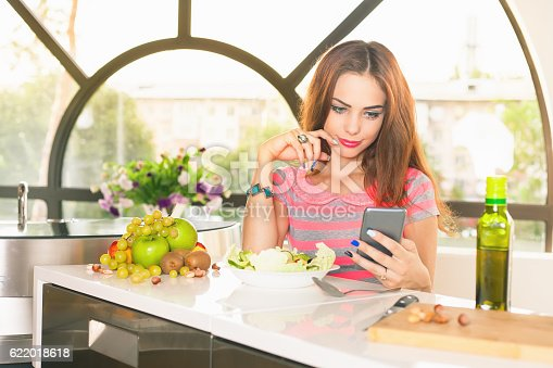 488109116istockphoto How to cook. Attractive girl cooking, looking recipe in internet 622018618