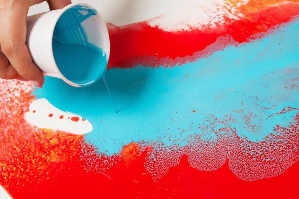 nasıl akrilik boyama yapmak. çalışmalar devam ediyor. mavi boya ile plastik bir bardak tutan kadın el. - akrilik boyama stok fotoğraflar ve resimler