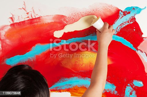 istock How to make acrylic painting. Work in progress. Female hand holding a plastic cup with yellow paint. 1159075648