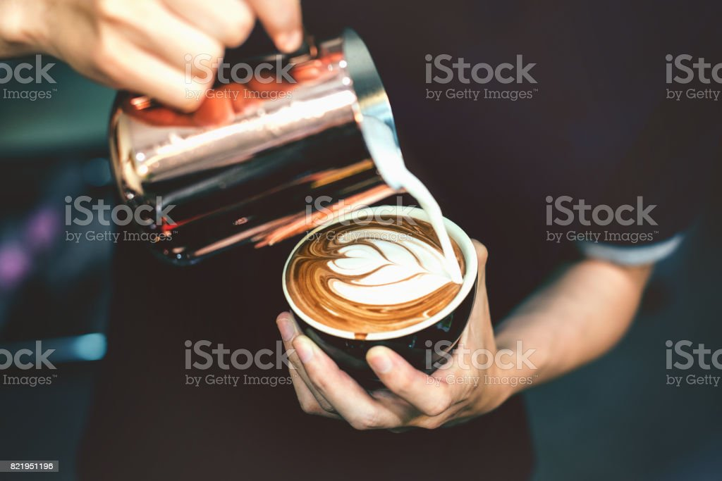 How to make latte art by barista focus in milk and coffee in vintage color tone. stock photo