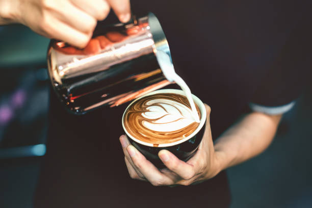 how to make latte art by barista focus in milk and coffee in vintage color tone. - coffee stock pictures, royalty-free photos & images