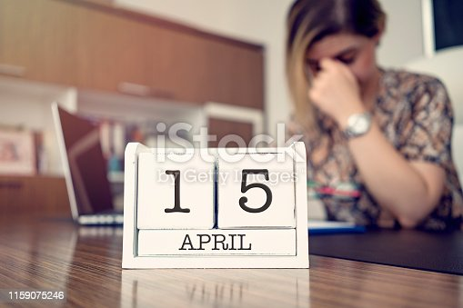 Fifteenth of April Tax Day. Young businessman thinking about new year taxes at her office.