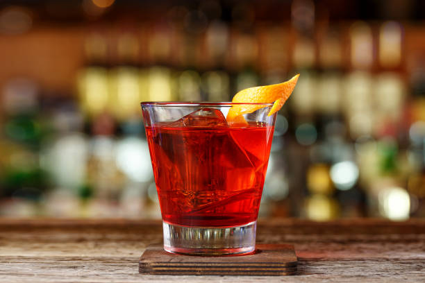 How to prepare a Negroni cocktail. Classic recipe with gin, campari and martini rosso. stock photo