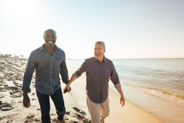 How to Retire Happy Senior couple  on the beach gay person stock pictures, royalty-free photos & images