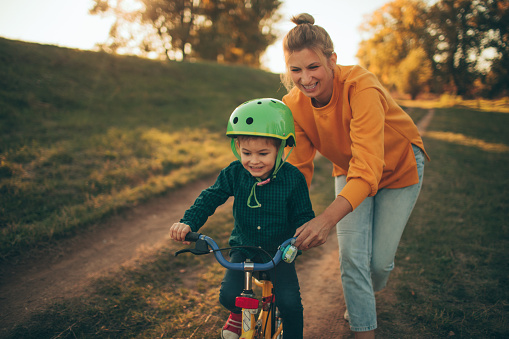 Photo of a young boy who is learning to ride a bicycle with a little help from his mother