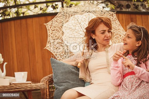 Mother and daughter are talking while relaxing in the garden. The woman is holding lace parasol on this sunny afternoon.