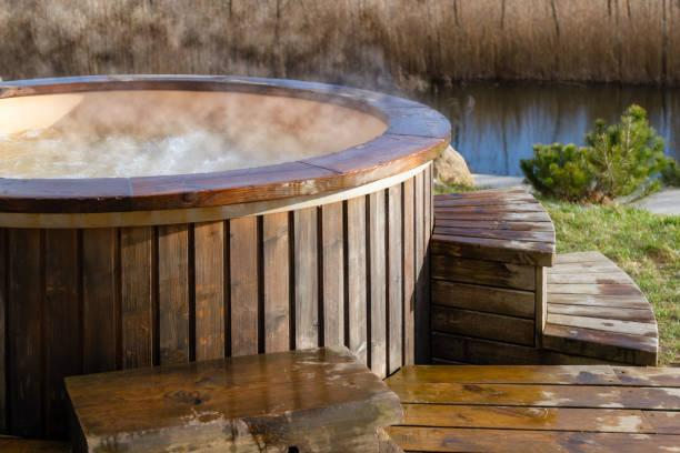 Wie Wasser im hölzernen Whirlpool draußen in der Natur wirbelt. Genießen Sie einen heißen Dampfpool an einem sonnigen Tag, private Spa-Behandlung. Niemand – Foto