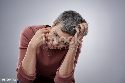 Studio shot of a mature woman looking stressed out against a gray background