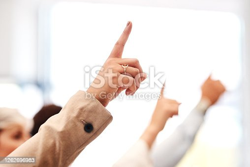 Closeup shot of a group of unrecognisable businesspeople raising their hands