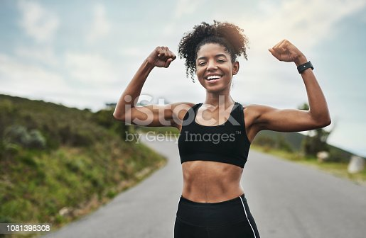 Cropped portrait of an attractive young sportswoman flexing her biceps outside