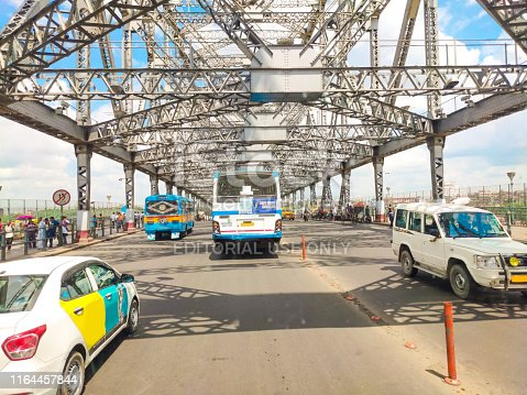 This is the image of howrah bridge and the image was taken from a running bush in a sunny day.Cars and bushes are cross the bridge and going to kolkata city from Howrah.